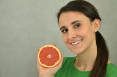Beautiful young girl is holding a red grapefruit Stock Photos