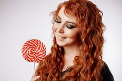 Pretty young curly redhead woman holding big sweet lollipop. Beautiful young girl holding a red white lollipop and smiling. Pretty happy curly redhead woman stock photos