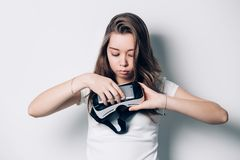 Beautiful young girl holding a virtual reality headset, puts the phone, rendered with a serious face. Computer technology that simulates a physical presence Royalty Free Stock Photography