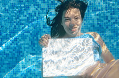 Beautiful young girl holding white blank board in swimming pool under water, family vacation Royalty Free Stock Image