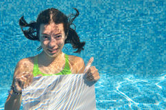 Beautiful young girl holding white blank board in swimming pool under water, family vacation Stock Images