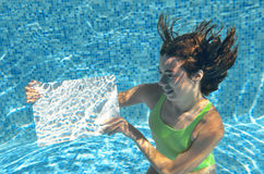 Beautiful young girl holding white blank board in swimming pool under water, family vacation Stock Photos