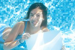 Beautiful young girl holding white blank board in swimming pool under water, fun on family vacation Royalty Free Stock Photography