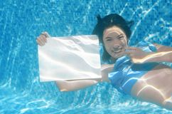 Beautiful young girl holding white blank board in swimming pool under water, fun on family vacation Stock Photos
