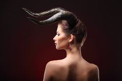 The beautiful young girl with horns like devil or angel Royalty Free Stock Photos