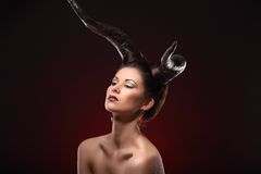 The beautiful young girl with horns like devil or angel Stock Image