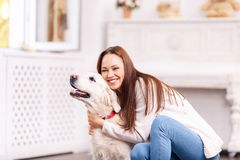 Beautiful young girl hugging her dog cheerfully. Moment of total happiness. Young attractive girl is laughing cheerfully while hugging her pretty cute dog Royalty Free Stock Photo