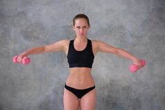 Beautiful young girl with an ideal figure and dumbbell doing exercises Stock Photo