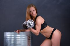 Beautiful young girl with an ideal figure and dumbbell in hand leans the elbows on barrel Stock Images