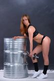 Beautiful young girl with an ideal figure and dumbbell in hand leans the elbows on barrel Royalty Free Stock Photos