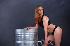 Beautiful young girl with an ideal figure and dumbbell in hand leans the elbows on barrel Royalty Free Stock Images