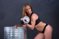 Beautiful young girl with an ideal figure and dumbbell in hand leans the elbows on barrel Royalty Free Stock Image