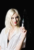 Beautiful young girl in the image of nurse with syringe in hand Royalty Free Stock Image