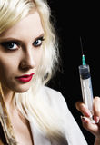 Beautiful young girl in the image of nurse with syringe in hand Stock Images