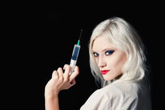 Beautiful young girl in the image of nurse with syringe in hand Stock Photography
