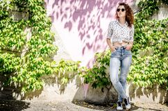 A beautiful young girl in jeans, sneakers and a shirt stands against the background of a multicolored wall, interwoven with grapes. A beautiful young girl in stock image