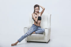 Beautiful young girl in jeans and top posing in leather armchair Royalty Free Stock Photos