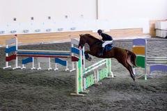 Beautiful young girl jockey riding horse. ready to pounce Royalty Free Stock Image