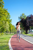 Beautiful  young girl jogging outdoor along trees path Royalty Free Stock Image