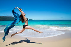 Beautiful young girl jumping with waving blue cape, scarf, on tropical beach royalty free stock images