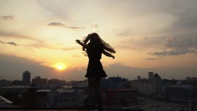 The beautiful young girl jumps with the raised hands and smiles against the background of the evening city. the girl on