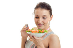 Beautiful young girl keeps near the face plate with vegetable salad and a close-up of a smiling. On white background Stock Photo