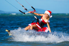 Beautiful young girl on the kite in the costume of Santa Claus. Royalty Free Stock Images