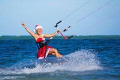 Beautiful young girl on the kite in the costume of Santa Claus. Stock Photo