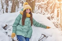 Beautiful young girl in knitted hat on winter forest background stock photo