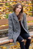 Beautiful young girl with large autumn sad eyes in a coat and ripped black jeans sitting on a bench in autumn park Royalty Free Stock Images