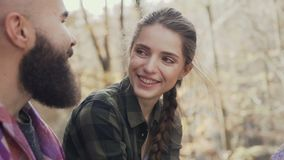 Beautiful young girl laughing happily, to a beautiful guy wearing a beard. Autumn Walking Youth