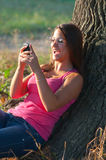 Beautiful young girl laughs while reading message Stock Image