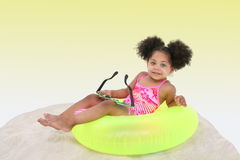 Beautiful Young Girl Laying In the Sand on Floaty stock image