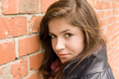 Beautiful young girl lean on red brick wall 2 Stock Photography
