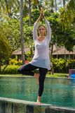 Beautiful young girl in leggings and tunic makes yoga practice, meditation, standing pose on the swimming in Bali island Indonesia royalty free stock images