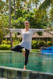 Beautiful young girl in leggings and tunic makes yoga practice, meditation, standing pose on the swimming in Bali island Indonesia royalty free stock photography