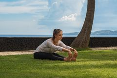 Beautiful young girl in leggings and tunic makes yoga practice, meditation, stretching asana on the ocean beach in Bali Indonesia stock image