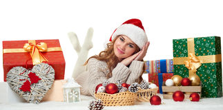 Beautiful young girl lie in santa hat with gift boxes - holiday concept Royalty Free Stock Images