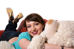 The girl lies with a teddy bear. The beautiful young girl lies on sofa with a teddy bear on a white background Royalty Free Stock Photos