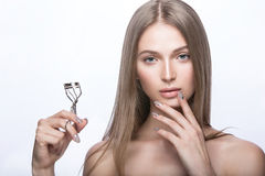 Beautiful young girl with a light natural make-up and beauty tools in hand. Royalty Free Stock Images