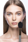 Beautiful young girl with a light natural make-up and beauty tools in hand. Stock Photography