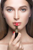 Beautiful young girl with a light natural make-up and beauty tools in hand. Stock Images