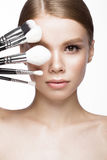 Beautiful young girl with a light natural make-up, brushes for cosmetics. Beauty face. Royalty Free Stock Image