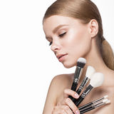 Beautiful young girl with a light natural make-up, brushes for cosmetics and French manicure. Beauty face. Royalty Free Stock Photo