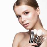 Beautiful young girl with a light natural make-up, brushes for cosmetics and French manicure. Beauty face. Royalty Free Stock Photography
