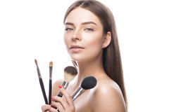 Beautiful young girl with a light natural make-up, brushes for cosmetics and perfect skin. Beauty face. Beautiful young girl with a light natural make-up stock images