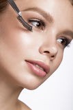 Beautiful young girl with a light natural make-up, Eyebrow Tweezers and False eyelashes. Beauty face. Stock Photography