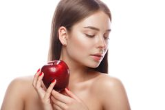 Beautiful young girl with a light natural make-up and perfect skin with apple in her hand . Beauty face. royalty free stock image