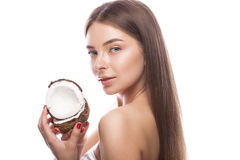 Beautiful young girl with a light natural make-up and perfect skin with coconut in her hand . Beauty face. stock image