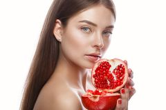 Beautiful young girl with a light natural make-up and perfect skin with pomegranate in her hand . Beauty face. royalty free stock photography